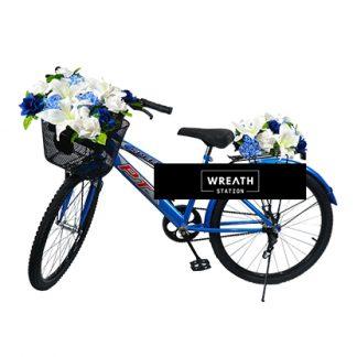 พวงหรีดจักรยานสีฟ้าประดับด้วยดอกไม้สีขาว