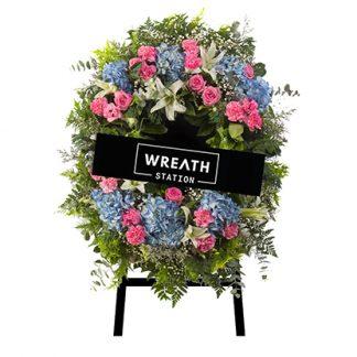 พวงหรีดดอกไม้หลากสีสัน ล้อมรอบไปด้วยดอกไฮเดรนเยียสีฟ้า และดอกกุหลาบสีชมพู สดใสเหมือนอยู่ท่ามกลางทุ่งดอกไม้