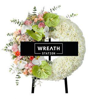 พวงหรีดดอกไม้สดทรงกลม ที่ประกอบด้วยดอกไลเซนทัสและดอกไฮเดรนเยียสีชมพู จากร้านหรีดสเตชั่น