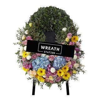 พวงหรีดดอกไม้สด หลากสี ประดับด้วยดอกไฮเดรนเยียสีฟ้า ดอกเยอบีร่าสีเหลือง ดอกกุหลาบสีม่วง ฯลฯ จากหรีดสเตชั่น