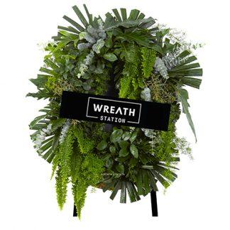 พวงหรีดดอกไม้สดขนาด 80-90 cm. ล้อมรอบไปด้วยใบไม้เขียวขจีอย่างใบฟิโลมะละดอ ใบซานาดู เฟิร์นขนนก ฯลฯ