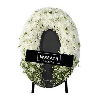 พวงหรีดโทนสีขาว ล้อมรอบด้วยดอกเบญจมาศ ดอกมัม ดอกสแตติส และดอกคัตเตอร์แสนบริสุทธิ์