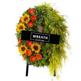 พวงหรีดสีจัดจ้าน ประดับด้วยดอกทานตะวัน ดอกเยอบีร่า ใบหลิวสีทอง ร้อนแรงและมั่นคง จากหรีดสเตชั่น
