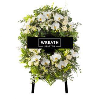 พวงหรีดดอกไม้บนกระดานดำ ล้อมรอบด้วยดอกกล้วยไม้ฟาแลนด์ ลิลลี่ และกุหลาบสีขาว สวย บริสุทธิ์ เหมาะอาลัยในทุกประเภท